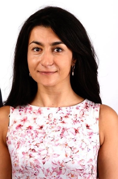 Photograph of Gesbeen Mohammad in white sleeveless dress with white background