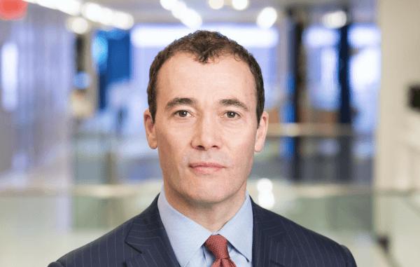 Portrait of William Lewis, CEO of Dow Jones in pinstripe suit, light blue shirt, red tie