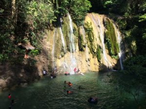 People swimming under the waterfalls set amidst nature in Philippines