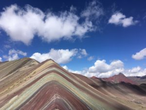 The colourful 'rainbow' mountain set against the backdrop of a clear blue sky, in Peru