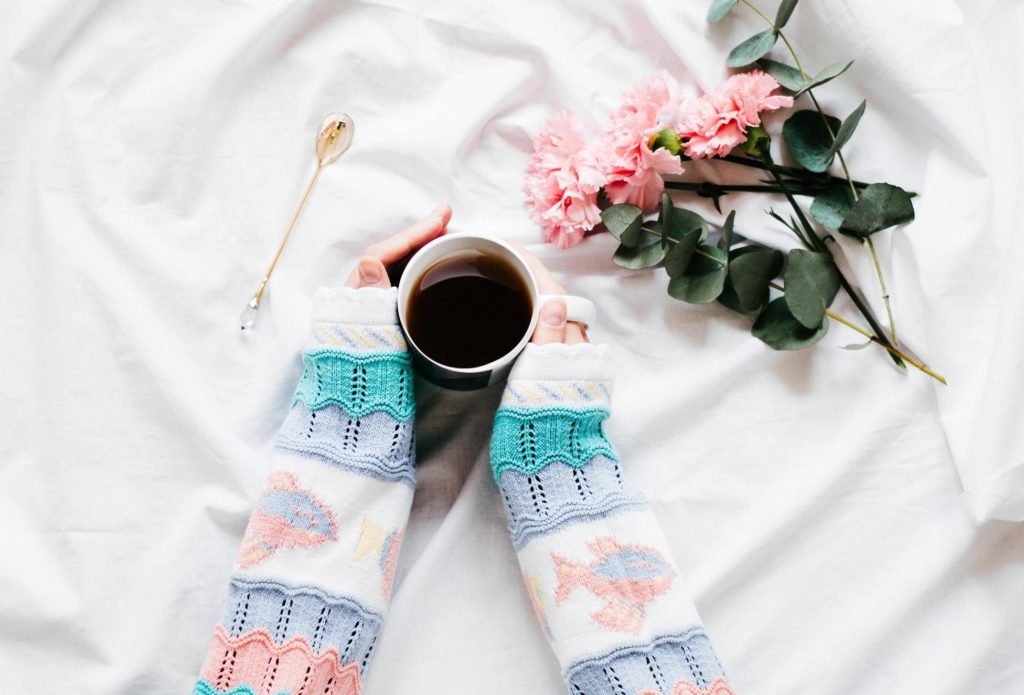 morning routine: Photograph of girl's arms wearing multi sweater holding mug with black coffee in bed, pink roses next to her