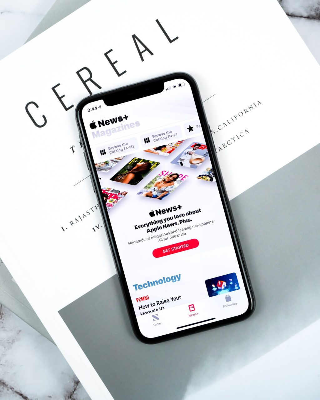 smartphone with Apple News open on top of white covered Cereal magazine